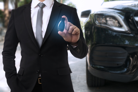 Businessman holding car key with Modern car on Background