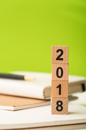 2018 wooden block number with business pen and paper note book .new year concept