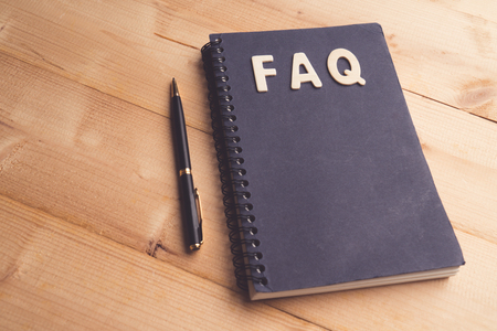 FAQ word with Black pen and book paper. Question and answer concept