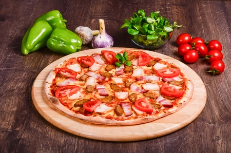 Meat pizza with tomatoes  on a table of dark wood