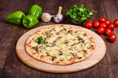 Thin pizza with mushrooms and cheese on a table of dark wood 免版税图像