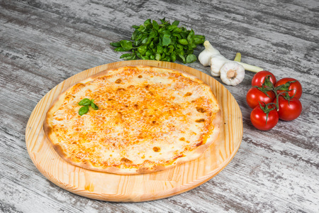 Italian pizza on a light wooden table on the background of vegetables and greens Imagens