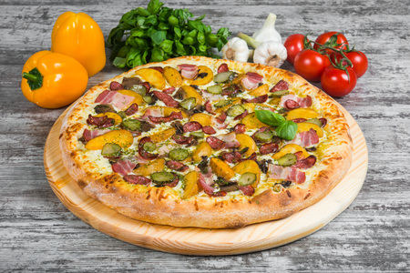 Italian pizza on a light wooden table on the background of vegetables and greens Фото со стока