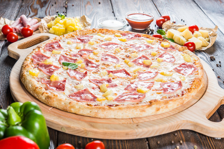 Big pizza with ham and pineapple on a round cutting board on a dark wooden background. Food ingredients. Macro