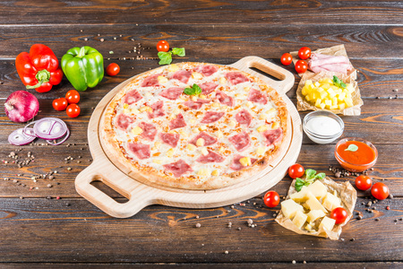 Big pizza with ham and pineapple on a round cutting board on a dark wooden background. Food ingredients.