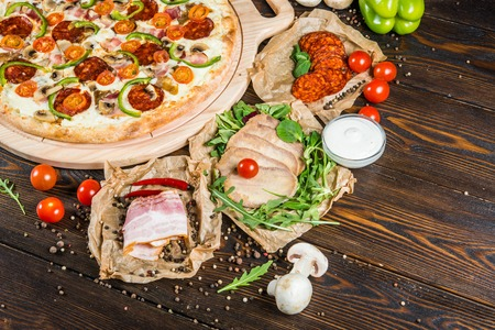 Large meat pizza with salami, bacon, mushrooms, tomatoes and paprika on a round cutting board on a dark wooden background. Ingredients. 写真素材
