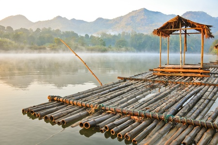riverside tree: A floating house with a smog in the morning ,kanchanaburi,thailand