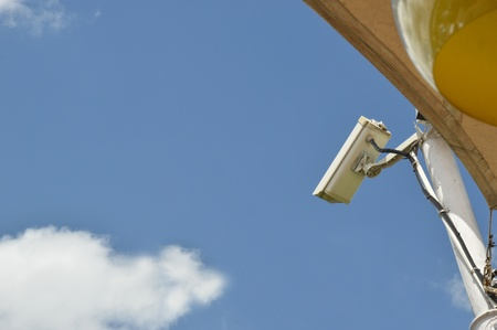 surveillance camera on blue sky background photo