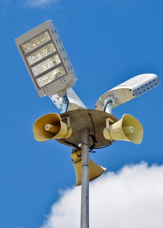 light bulb and loudspeakers on the pole with blue sky background photo
