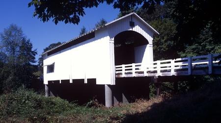 vintage: Earnest Bridge 1938 Lane County in Oregon, Vintagewit Covered Bridge. Witte overdekte brug met witte hek hekwerk in de aanloop naar het vangen van de zon. Redactioneel