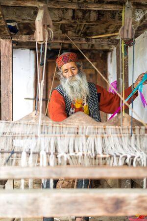 Kullu, Himachal Pradesh, India - 09 de agosto de 2018: Un anciano indio hace un tejido sadu tradicional. Hacer un pattu saris en el Himalaya Editorial
