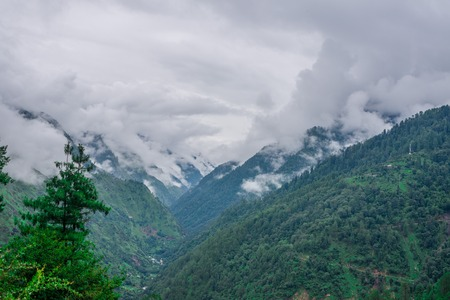 Photo of Tropical mountain range view. Timelapse Of Moving Clouds And Fog over Himalayan mountain range in Sainj, Kullu, Himachal, India 免版税图像