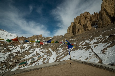 photo of tibetan flags in foreground in a village in spiti valley