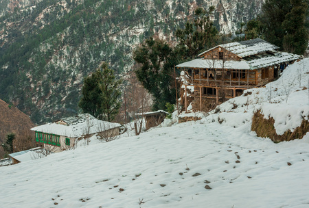 Snow covered wooden house in mountains - Majestic winter landscape in himalayas -