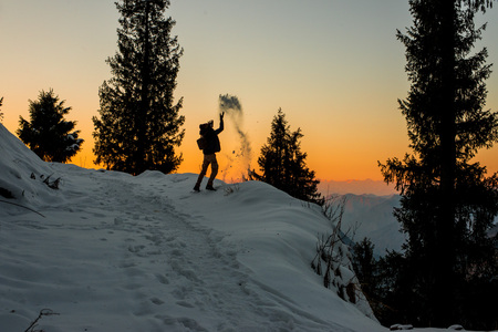 Kullu, Himachal Pradesh, India - January 09, 2019 : Traveler playing with snow over Sunset in himalayas