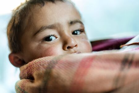 Kullu, Himachal Pradesh, India - December 21, 2018 : closeup of a poor staring hungry indian boy with sad expression on his face and his face and clothes are dirty