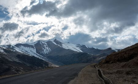 Road in mountains Himalayas and dramatic clouds on blue sky. Ladakh, Jammu and Kashmir, India
