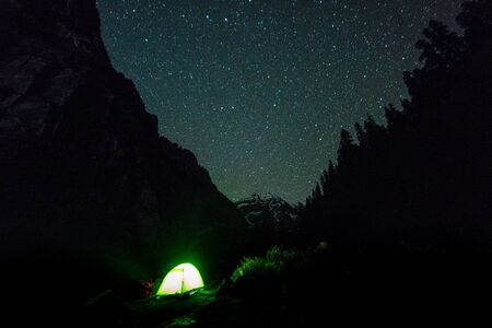 campfire under night sky with star on top of mountain surrounded by forest -