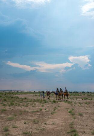 Jaisalmer, Rajasthan, India - July 29, 2019 : Tourist Camel Safari in Thar Desert -