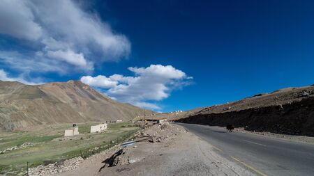 Road in mountains Himalayas and dramatic clouds on blue sky. Ladakh, Jammu and Kashmir 写真素材