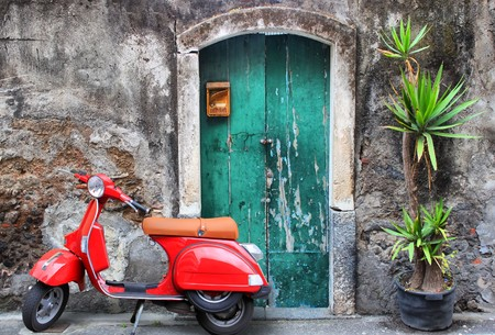 vespa: Foto de scooter rojo cerca de la puerta verde y Palma Foto de archivo