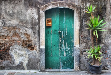 front of house: Photo of facade oh old house with green door and palm Stock Photo