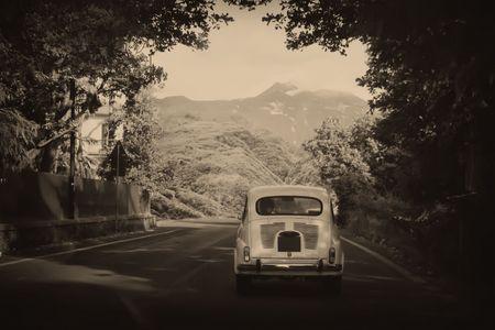 Sepia photo of a retro car going to mountains photo