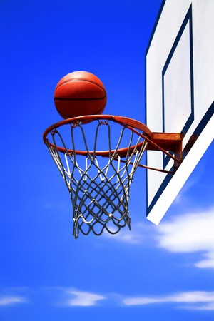 swish:  basketball hoop and blue sky in background Stock Photo