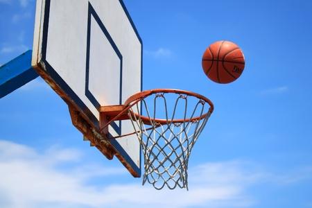 バック グラウンドでのバスケット ボールのフープと青空の写真