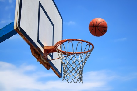 Photo of basketball hoop and blue sky in background Stock Photo