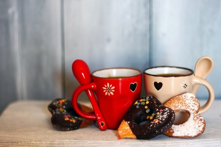 Photo of cute coffee cups with heart-shaped cookies photo
