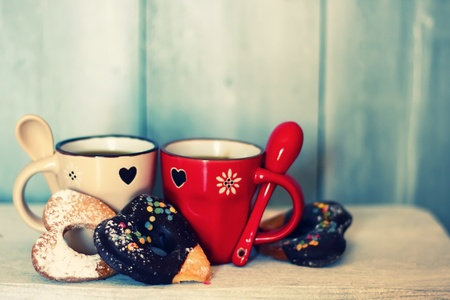 Photo of cute coffee cups with heart-shaped cookies