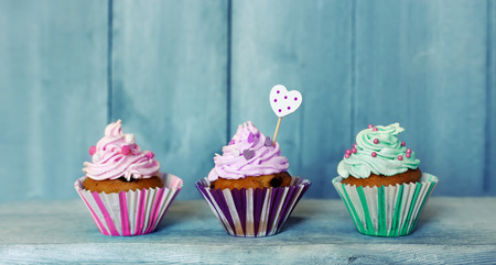 Photo of 3 cupcakes on wooden background Stock Photo