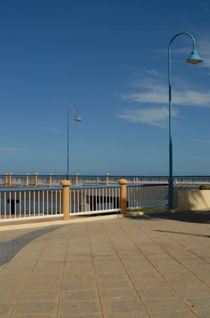 bollards: A people-free scene at the end of a modern pier, lamp posts,rails and bollards