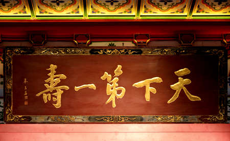 placa bacteriana: la caligrafía china en la placa de madera Editorial