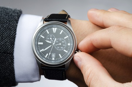 reloj: businessman adjusts the time on his wristwatch