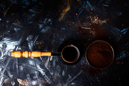 Ground coffee and coffee maker, dark background. Low key, top view