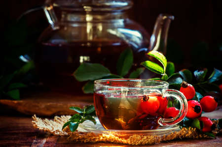 Curative tea with rosehip, folk medicine, Vintage wood background, selective focus