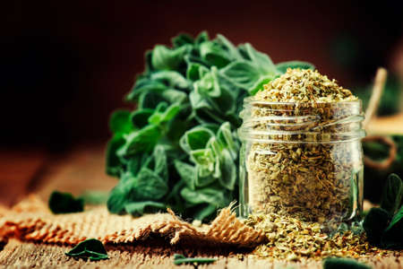 Dried and fresh oregano, vintage wood background, rustic style, selective focus