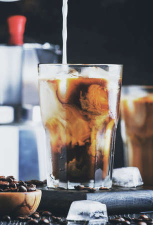 Coffee with ice and milk, brown table, selective focus and shallow DOF