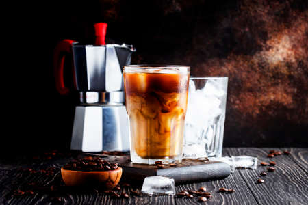 Summer cold coffee with ice and milk, brown background, selective focus and shallow DOF Standard-Bild