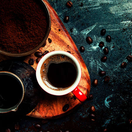 Ground coffee, Turkish coffee maker, cup with hot espresso on dark background, top view
