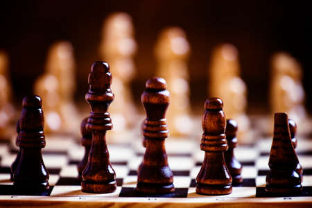 Chess pieces on a chessboard, black background, selective focus, shallow depth of field