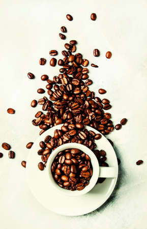 Roasted coffee beans in a white cup and saucer, gray food background, top view, flat lay Standard-Bild