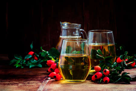 Healthy and useful drink from rose hip and apples, vintage wooden background, selective focus Banco de Imagens
