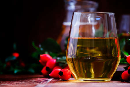 Healthy and useful drink from rosehip and apples, vintage wooden background, selective focus