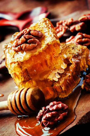 Autumn honey and walnuts, useful and delicious food, black background, selective focus, shallow DOF