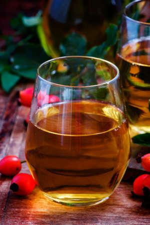 Rosehip drink, dark wood background, selective focus