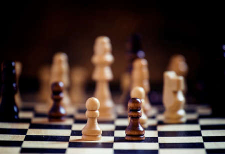 Chess pieces on a chessboard, black background, selective focus, shallow depth of field Imagens