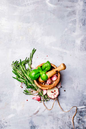 Herbs, spices, garlic and sea salt in a wooden mortar and pestle, a top view, food background